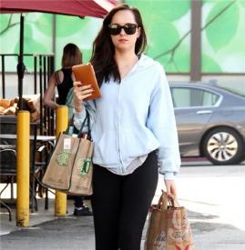 Dakota Johnson现身街头 天蓝色卫衣+黑色健美裤休闲味十足